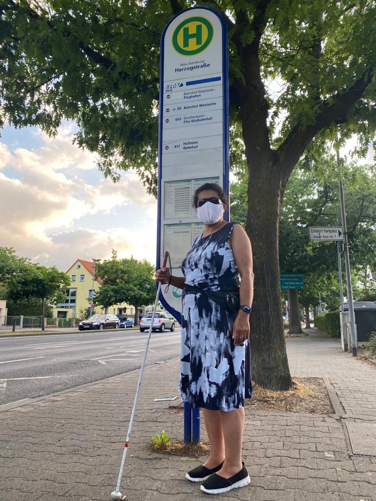 Lydia steht mit Maske und Blindenlangstock an einer Bushaltestelle