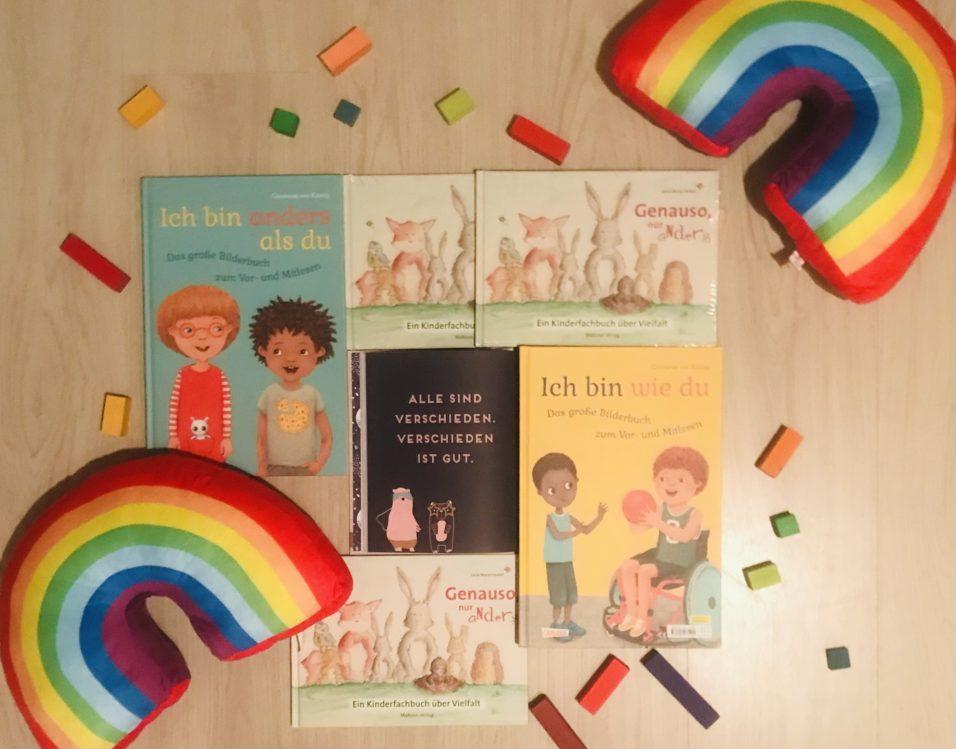 die vorgestellten Kinderbücher liegen in der Mitte, dazwischen ein Spruch: Jeder ist anders, anders ist gut. Ringsherum liegen 2 Regenbogenkissen und bunte Bausteine