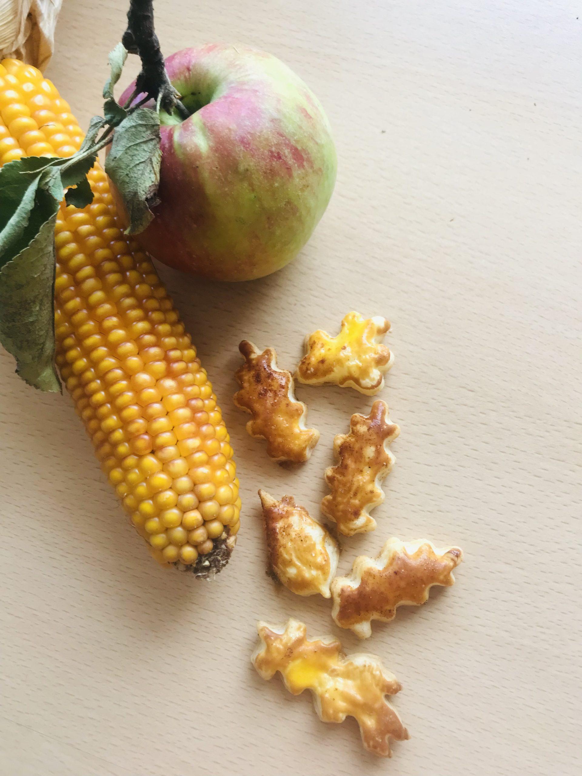 Ein Maiskoleben, ein Apfel und Blätterteigblätter