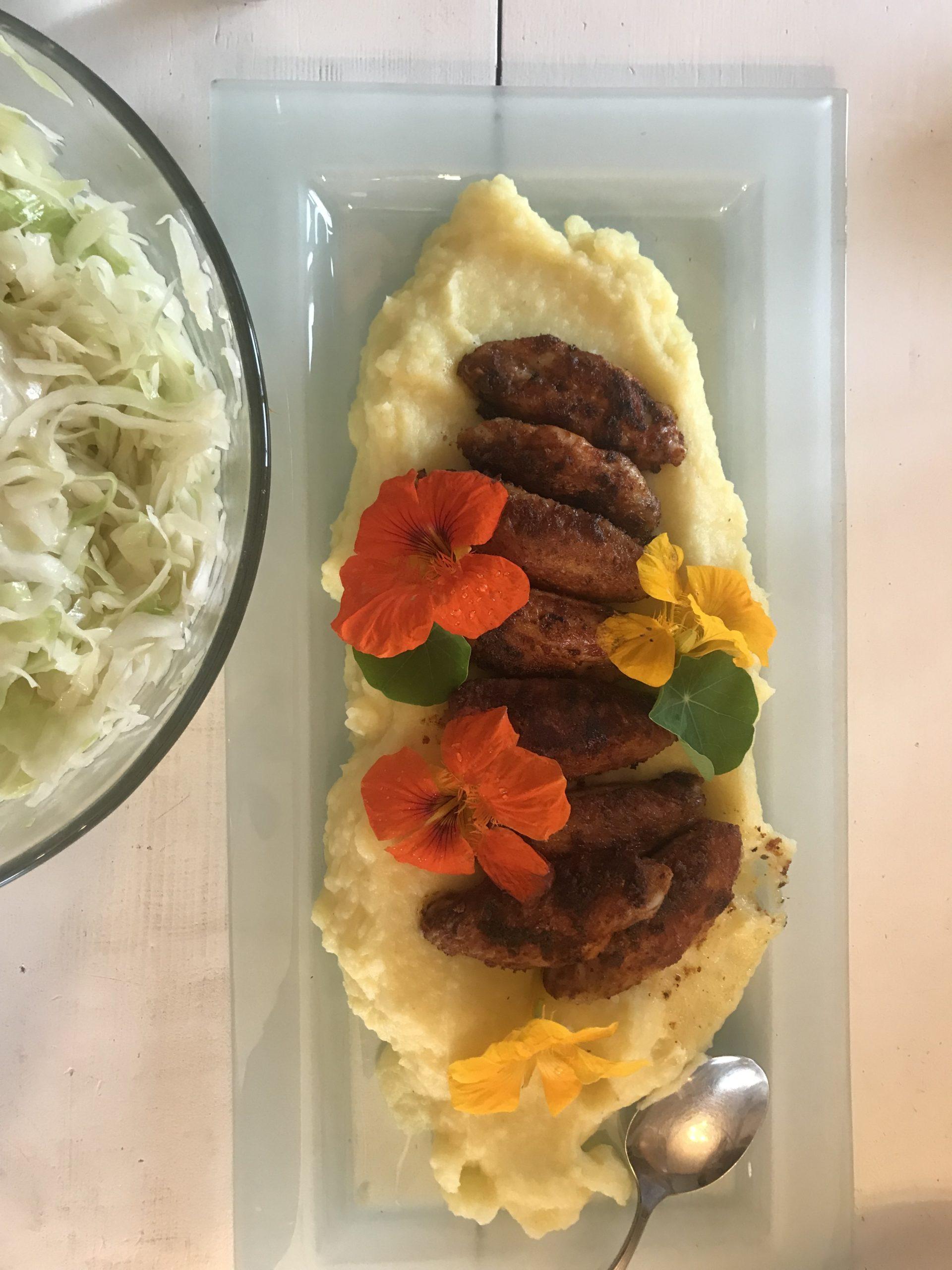 Kartoffelbrei mit Chickennuggets und Kapuzinierblüten auf einer Glasplatte