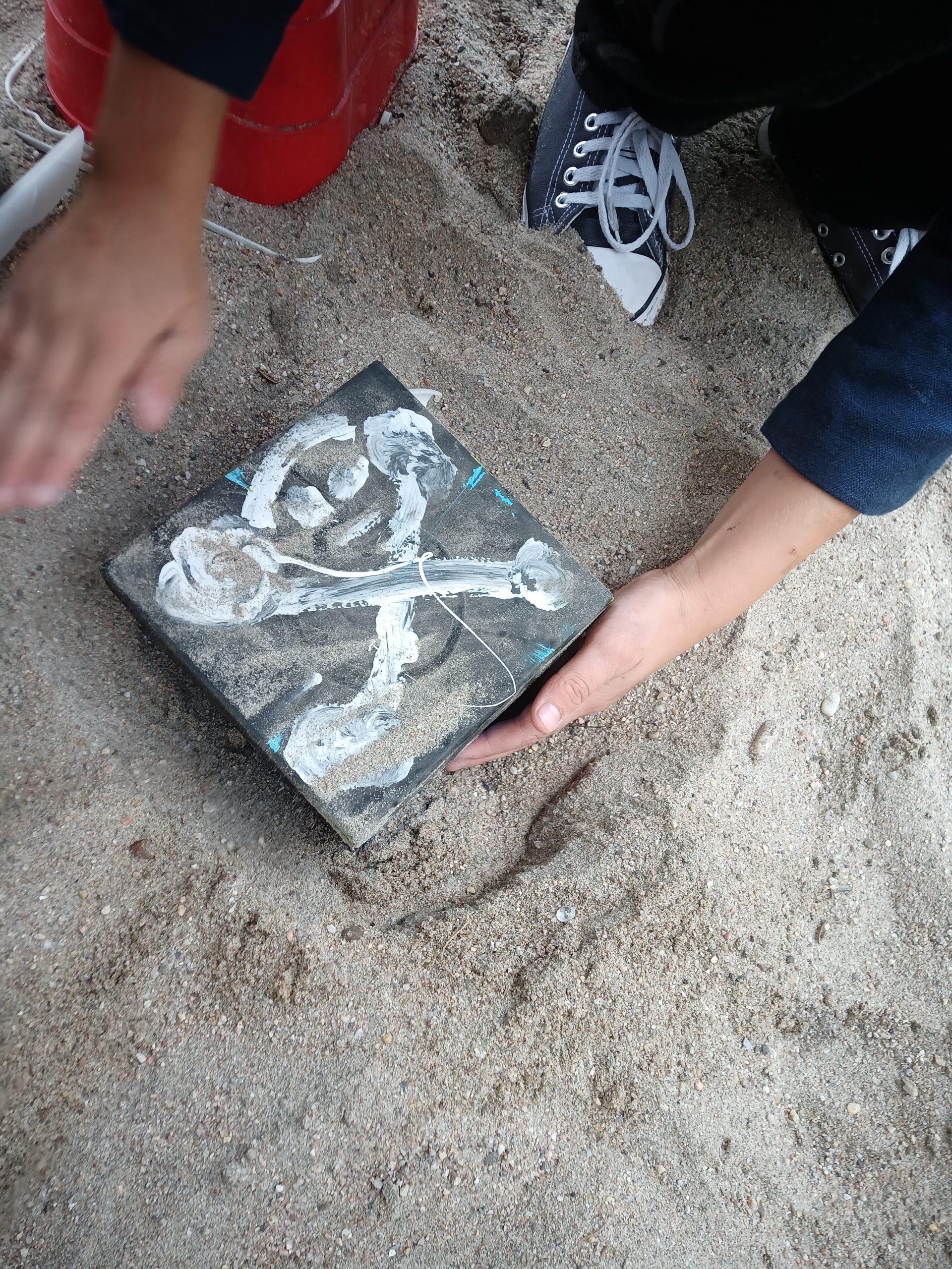 Die Kinder buddeln eine SChatzkiste mit einem Totenkopf aus dem Sand