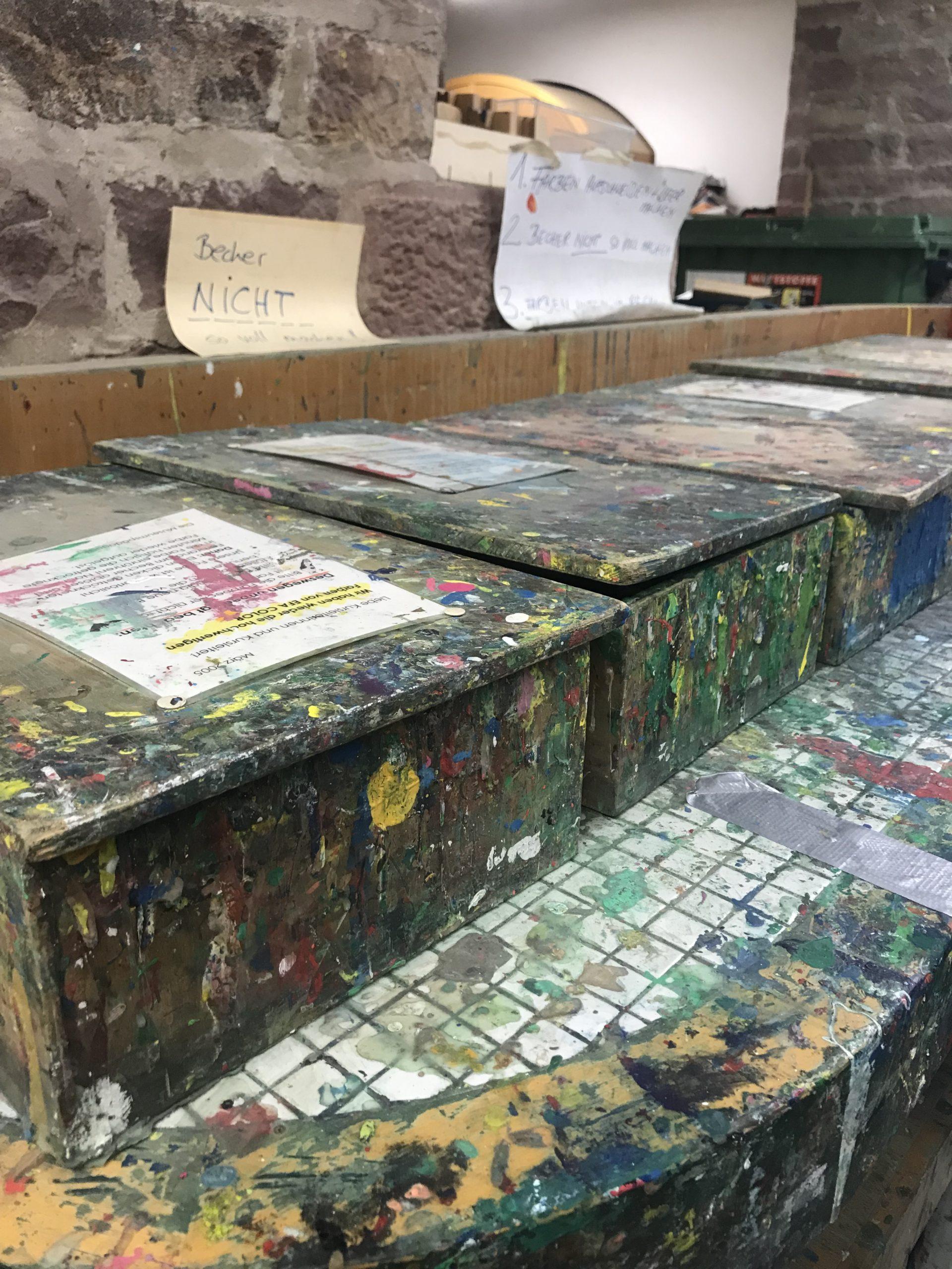 Viele Kisten im Kunstaltier, alle völlig mit Farbe bekleckert