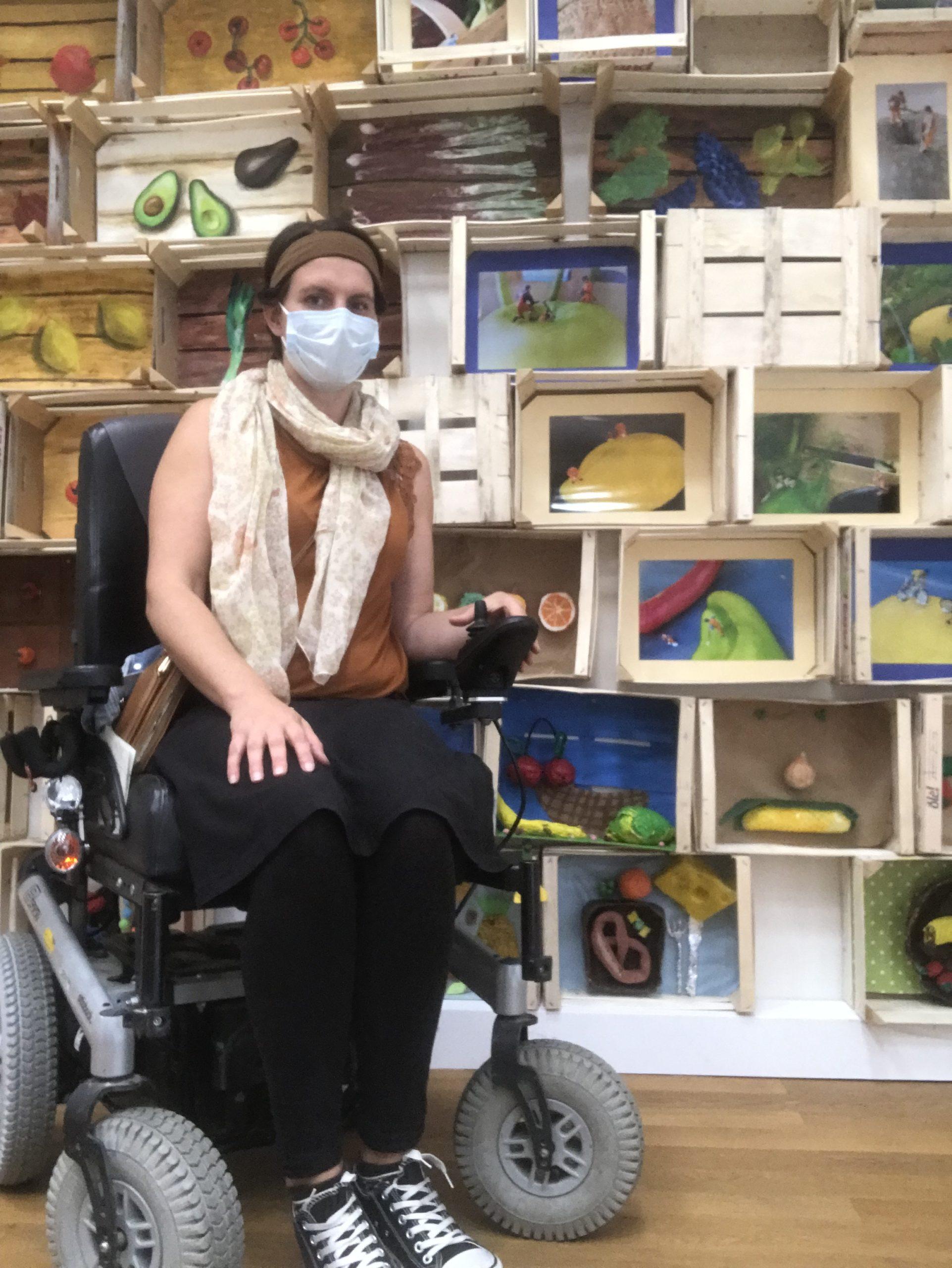 Ich sitze mit Mundschutz im Rollstuhl vor vielen Weinkisten. In diesen sind verschiedene Obstbilder von KIndern gestaltet